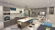 Open space. Cucina con penisola e divano angolare dai toni grigio e blu.