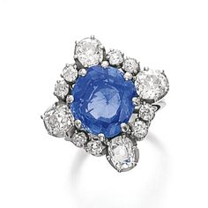 SAPPHIRE AND DIAMOND RING The cushion-shaped sapphire within a border of oval and circular-cut diamonds