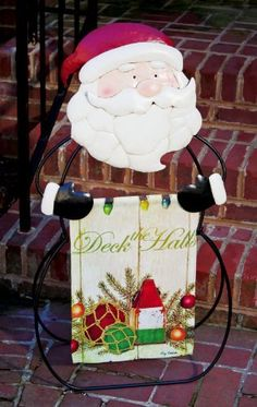 """35.75"""" Santa Standing Garden Flag Holder by Evergreen. $64.99. Santa Standing Garden Flag HolderItem #489239Standing black metal garden flag holder shaped as an outline of Santa Claus with his red hat and black gloves to hold the flagDimensions: 20""""L x 10""""W x 35.75""""DMaterial(s): metalNote: Flag shown is not included"""