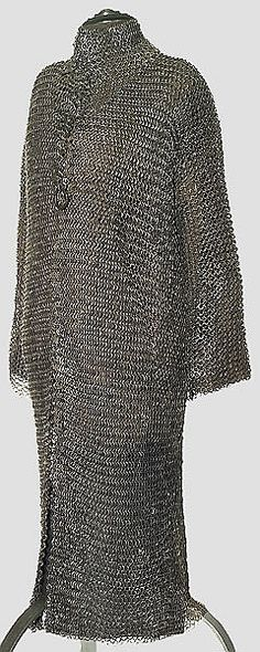 European riveted mail hauberk, 15th to 16th century, heavy long shirt with long sleeves, high collar with open neck, iron hook closures, heavy links on the chest, back and shoulders, sleeves and leg apron on lighter links. Alternating riveted and closed links with oval cross section, about 125 cm.  Early, over knee-length mail was worn in the Crusades to protect the entire body. A very similar dated copy in the collection of the Cleveland Museum of Art, Inv. CMA 1916.1817.