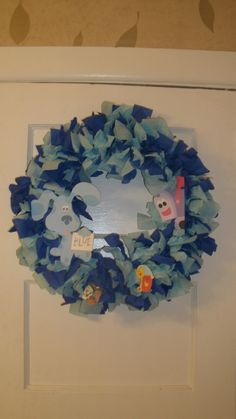 Wreath I made out of a coat hanger some tissue streamers from the $1 store and I cut out some pics from a book and glued them...  Its hard to find Blues Clues party stuff and this only cost me $2!!!