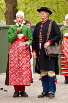 This couple is wearing folk costumes from Boda in Dalecarlia. She is wearing a white cap and the hymn book is wrapped in a piece of printed cotton. They are dressed for Church on Sunday.