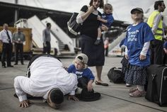 New life - A religious Jewish man from the United States kisses the ground next to his family after they disembarked a plane with other new Israeli immigrants at Ben Gurion airport, outside Tel Aviv, on July 23, 2013.