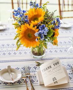 Blue and yellow wedding flower centerpieces with sunflowers.  Photo: Joshua Zuckerman Photography