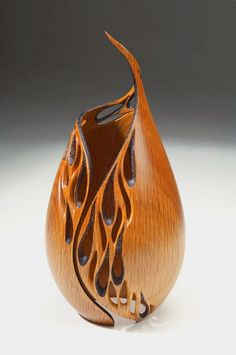 A flame shaped, made of earthy wood, hollowed to hold air and tear drop shaped cut outs to assimilate the water aspect. Great design.