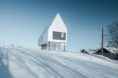 the all-white chalet features a sharp silhouette and lifted structure to almost disappearing into the landscape.