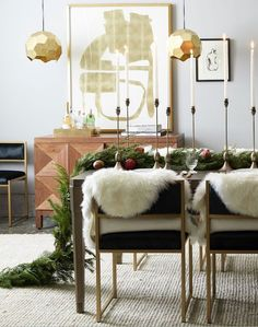 A gorgeous modern holiday dining room with gold pendant lights, a geometric credenza, velvet dining chairs topped with sheepskins and a lush greenery garland table runner.