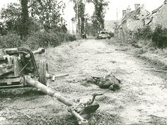 a good but sorry sight after the battle, summer 1944 France. An obvious Waffen SS solider lay dead next to the Pak gun (most likely the HitlerYouth Division, and if so, the solider could not be more than 19 years old).   In the distance, one can see two tanks, one bing a German paned.  No visible damage to the tanks though.