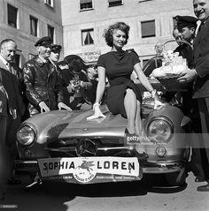 Italian actress Sophia Loren on the hood of a car at the Rally of Cinema III, Rome, 1956.