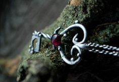 Srebrna zawieszka w kształcie klucza, z motywami serca tu i ówdzie :) W centralnym punkcie umieściłam granat. / Silver pendant in a shape of the key with some hearts. The stone in the center is a garnet.