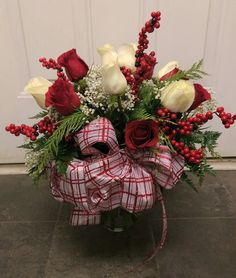 Red and White Roses arranged in a vase. Completed with Holiday bow and berries.