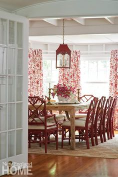New England Home Red Chinese Chippendale chairs and a red Chinese lantern lighting fixture add Chinoiserie style to this charming dining room.