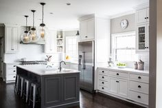Illuminated by large glass globe pendants, his wonderfully designed gray and white kitchen features a charcoal gray island topped with a white quartz countertop finished with a corner prep sink with a polished nickel faucet.