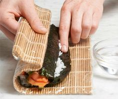 Rolling sushi and dampening edge with water