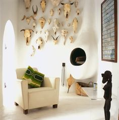 Bleached bovine and other skulls mounted on stark white walls. Floating kiva fireplace. Southwestern cool