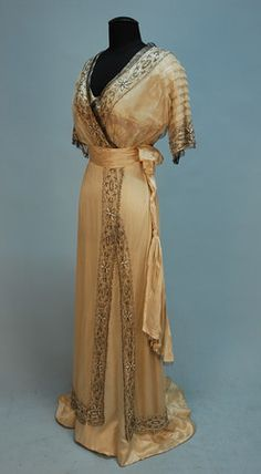 SILK and BEADED NET GOWN, c. 1911. Ivory satin beneath cream net having pleated short sleeve and V-neck decorated with bands of crystal and opalescent white beads in a pattern of daisies, with beaded fringe