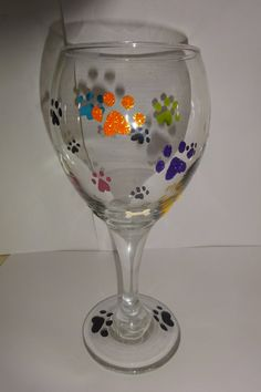 Hand Painted Wine Glass with multicolored paw prints and bones. Each glass is hand painted, air dried and then baked.  Each glass is about 7.25 inches tall and 10.75 oz  *Hand wash only*  Each glass is personally hand painted, so placement of paws and bones may vary slightly per glass.  Please allow up to 3-5 business days for processing plus shipping time, although I will try to process each order sooner than that if possible.