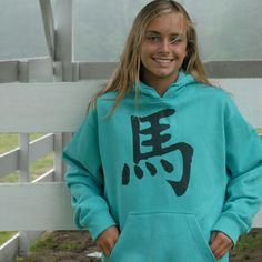 """The large graphic Japanese character, called a """"Kanji"""" translates to the word """"horse!"""" Our cotton/poly, peacock blue hooded sweatshirt, with..."""