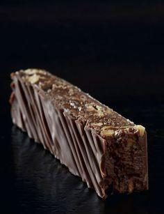 Barre pralinée Préparation : 40 minutes + 1 heure de reposCuisson : 10 minutes  Les ingrédients: Pour le praIiné :1/2 gousse de vanille  200 g de sucre semoule300 g de noisettes entières230 g de chocolat au lait80 g de noisettes hachées grillées Pour l'enrobage :250 g de chocolat au lait à 32-40 % de cacao tempéré  Les étapes pour la préparation de la barre pralinée: 1. Le pralinéPréchauffez votre four à 170 °C (th. 5-6). Versez les noisettes sur une plaque couverte de papier sulfurisé…