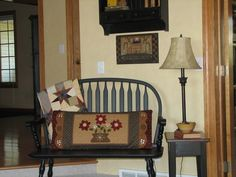 Star quilt & long applique pillow displayed on a bench