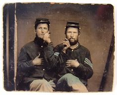 Can I give you a hand with your cigar? Two unidentified soldiers in Union uniforms holding cigars in each others' mouths, photographed between 1861 to 1865. The uniform of the solider on the right has blue chevrons which would rank him as an Infantry Sergeant. (History By Zim)