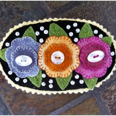 Wool pin...colorful...love the French knots or beads in the background.