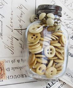 Old glass jar filled with vintage utility buttons.