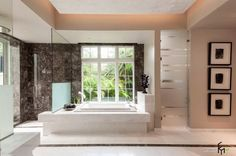 a luxurious bathroom with black marble wall with concrete bathtub and glass showering room with fascinating wall decors