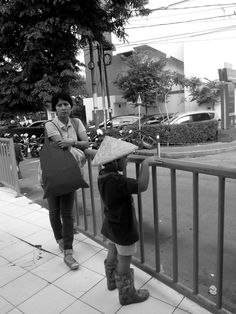 black and white mother and son waiting bus