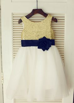The materials for this dress is sequin,satin and tulle.The listed color is gold top,ivory skirt with navy blue flower sash.The sash is folded and has a handmade flower at front.It is in knee length.Perfect for wedding party,prom,photo shoot,Easter or daily wear.For Custom Dress, please enter the mea