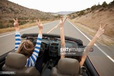 Hands up, while driving a convertible.