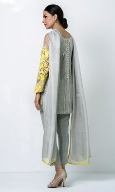 Set on a base of ash grey cotton net, this three piece ensemble features canary yellow embroidery with crystal embellishment and cutwork at the bottom. Comes with ash grey trousers in pure raw silk with crystal buttons and a net dupatta. Pakistani Gowns, Simple Pakistani Dresses, Pakistani Fashion Casual, Pakistani Dress Design, Dress Neck Designs, Bridal Blouse Designs, Bollywood Outfits, Bollywood Fashion, Frock Fashion