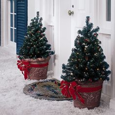 Mini lighted trees in terra cotta pots with added bright red ribbons for the porch entry. Add a festive door mat  and what could be simpler for a warm Christmas welcome?