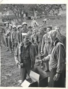 1943- U.S. soldiers get coffee and donuts from Red Cross girls just behind the front lines in Italy.