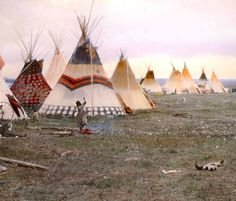 Woman chopping firewood, Eagle tipi in foreground, Star tipi on left. Blackfoot camp. Early 1900s.   Glass lantern slide by Walter McClintock.