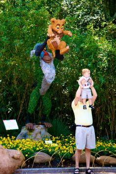 A dad and his baby imitate this Lion King statue at Disneyworld