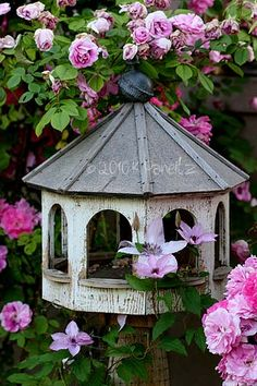 Pink roses, clematis and a vintage birdhouse - perfection in the garden!