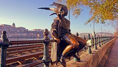 Kiskirálylány – это очаровательная скульптура маленькой девочки в карнавальном костюме шута, сидящей на перилах трамвайной остановки. За её спиной...