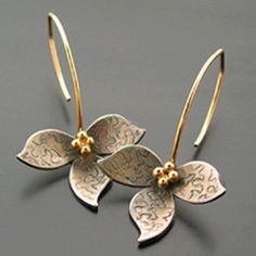"""Patinaed sterling lotus dangles from a 1 1/4"""" gold filled wire. Lotus is 3/4"""" wide and center beads are solid 14k."""