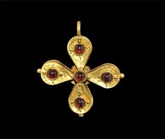 """5th-8th century AD . A fabricated hollow gold pendant formed from four piriform elements each with a cabochon garnet to the centre and gold loops surrounding; a fifth garnet to the centre, granules to the outer edges and filigree border behind. 3.91 grams, 35 mm (1 1/4""""). Silk collection, London, UK; formed in the 1950s."""
