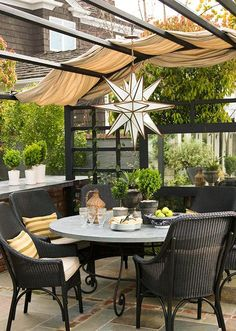 Loving the outdoor-sy feel!  Outdoor-friendly fabric draped over a pergola create shade and shelter from rain. A neutral color palette -- here black, gray, and beige -- work with any color scheme. A lantern creates wonderful ambiance for entertaining in the evening or at night.  Mixed materials -- here brick and flagstone -- create a stylish patio floor.