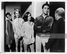 Elvis Presley feigns indignation as he complains to motel manager John Fiedler about a noisy party in the room shared by girls Lynn Edginton, Chris Noel, and Shelley Fabares in a scene from the film 'Girl Happy', 1965.