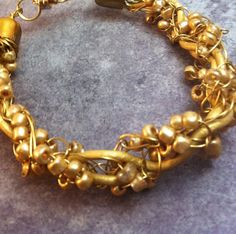Tones of gold bracelet created with seed beads, wire, and gold cording.
