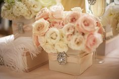 Blush Centerpieces   a more embellished look but the sweetly layered flowers are still being used as they're key to the blush pink look. The fabric covered containers, wrapped with ribbon and decorated with sparkles are at the uber glam end of the blush pink scale. The addition of the cream flowers add some nice depth to the arrangement as well which is almost essential to help that pale pink pack a little more punch