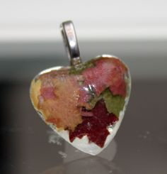 Real leaves cut from a leaf paper cutter and put in resin pendant
