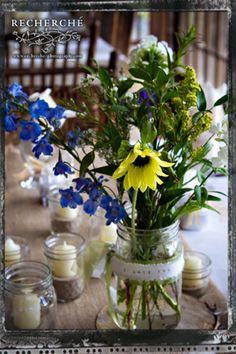 Wildflower Centerpiece: Bella delphinium, sunflowers and yellow solidago with Italian ruscus.