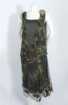 Evening Dress, mid 1920's. The under layer is a slip of black satin; the outer layer is fashioned from black knotted net lace embroidered with black silk floss leaves and a zigzag pattern of burnished gold floss, with a large gold lamé rose at the shoulder and the black-and-gold Deco clasp at the hipline.