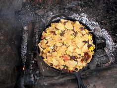 Campfire Nachos - use a cast iron skillet to heat nachos topped with refried beans, corn, cheese, whatever!  Cover with foil & heat until cheese is melted.  Nice change of pace for campfire food!