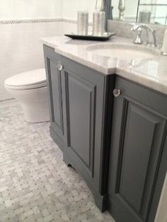 Stunning guest bath with gray bathroom vanity paired with carrara marble countertop and subway tile backsplash. Gray bathroom cabinets with crystal knobs and polished nickel faucet kit. Bathroom floor composed of marble basketweave tiles and subway tile baseboard. by patricé