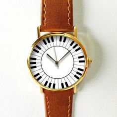 Ships Worldwide Type: Quartz Adjustable from 16.5 cm to 20.3 cm (6.50 inches to 8.0 inches) . If you want additional holes for adjustment, please make a note upon checkout or send me a convo Display: Analog Dial Window Material: Glass Case color : gold Case Material: Metal Case Diameter: 3.8 cm (1.49 inches) Case Thickness: 0.7 cm (0.27 inches) Band Material: quality sythetic leather with stitching for durability Band Width: 2.0cm (0.78 inches) Band Length: 23.5 cm (9.26 inches) Band Color…